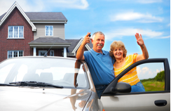 older couple standing next to car outside home